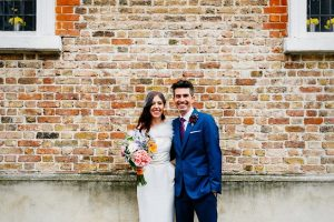 intimate wedding - Couple against brick wall